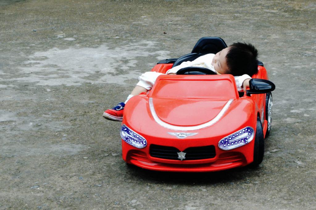 Merkwürdigkeiten aus China - schlafendes Kind in einem Spielzeugauto